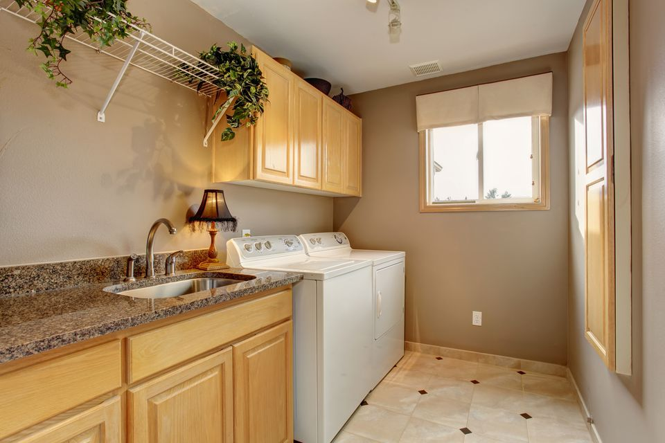 Traditional laundry room with nice counters and washer dryer com