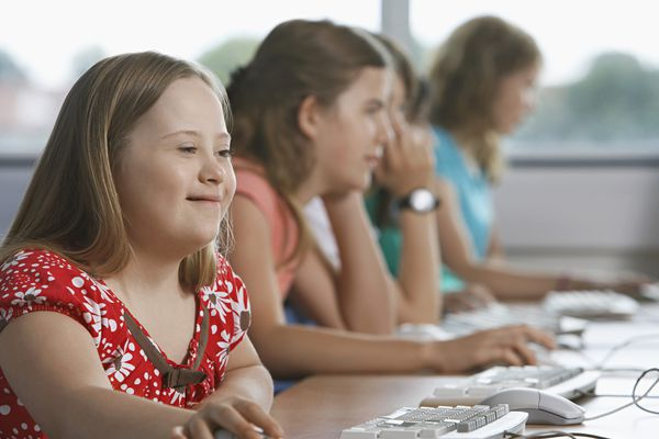 Girl (10-12) with Down syndrome using computer in computer lab, children in background
