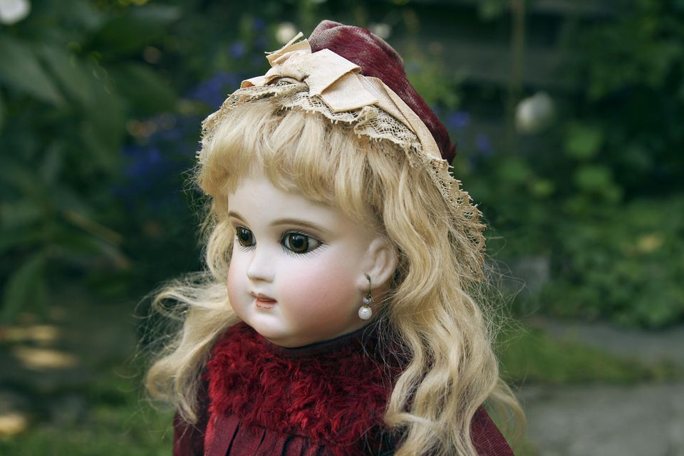 Portrait of beautiful antique French doll wearing red costume.