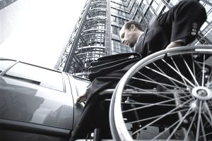 Wheelchair-using business executive turning key in car door, low angle.