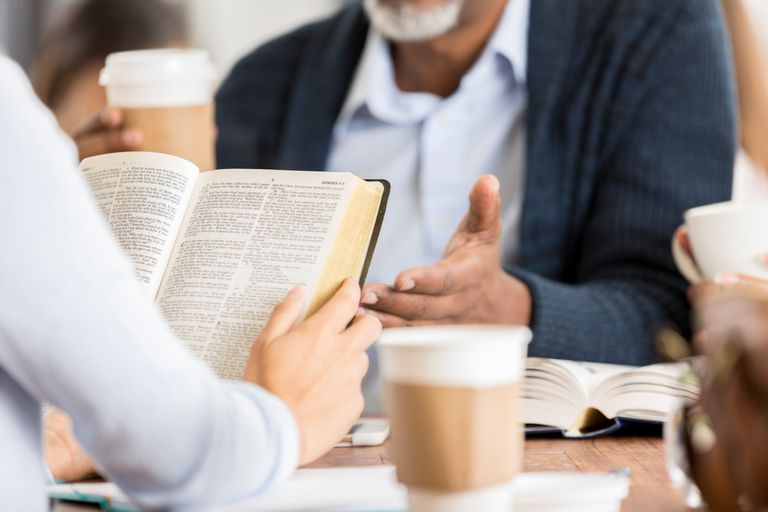 Unrecognizable people studying the Bible