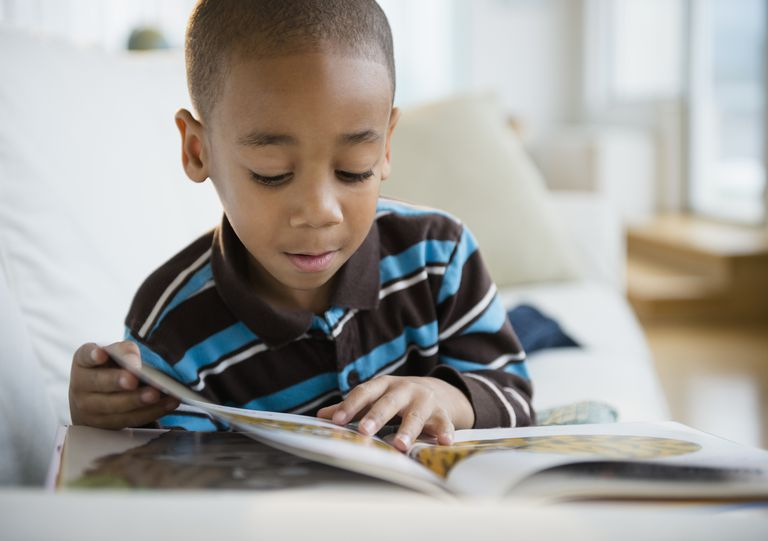 young boy reading book on sofa