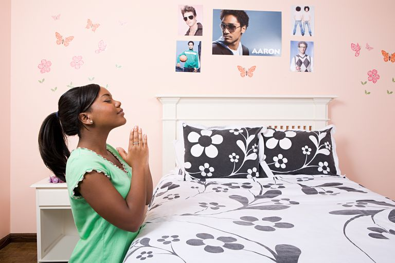 Girl praying in her bedroom
