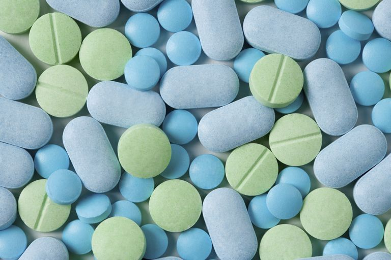 Pills of different shapes, colors and sizes fill the image.