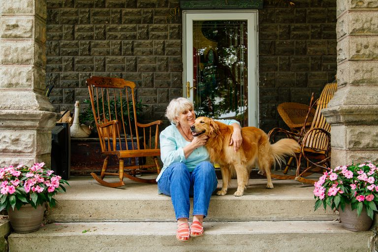 Older woman sitting on porch with dog