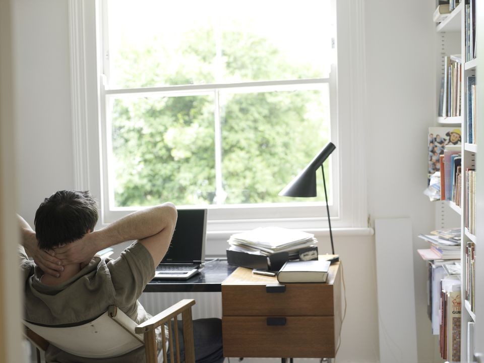 home office lighting. man leaning back in chair a home office lighting