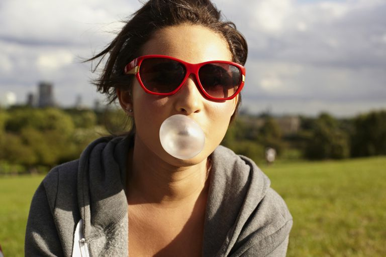 Teenage girl in sunglasses, blowing bubble gum