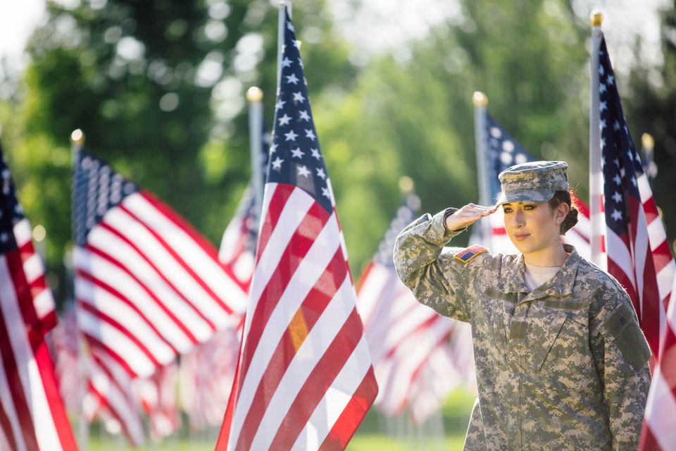 American Female Soldier saluting in front of American Flags