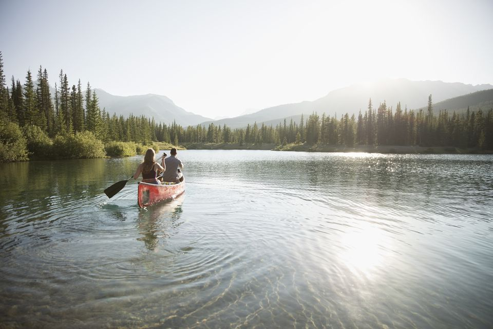a couple in a canoe on a lake in a park