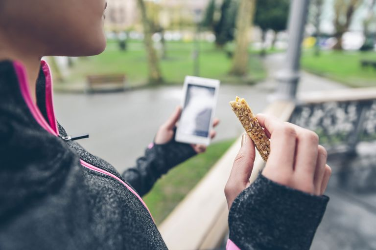 Young woman holding nutrition bar and cell phone after run