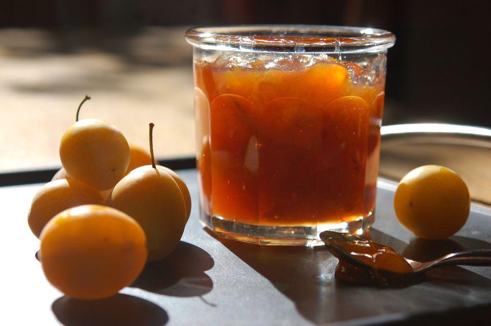 Plums next to a jar of plum jam