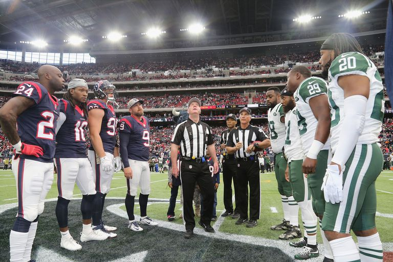 Referee John Parry #132 performs the coin toss with captains of the Houston Texans and the New York Jets at Reliant Park on November 22, 2015