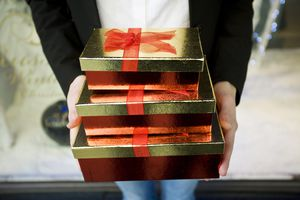 Shopper holding a stack of festive gift boxes