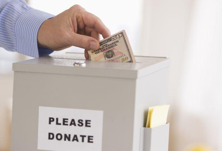 man putting money into charity donation box