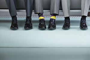 Business men's feet, one wearing crazy socks.