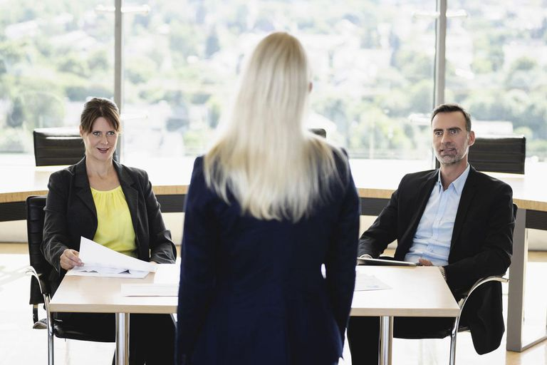 business people interviewing young business woman