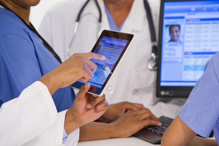 Doctors using digital tablet together in hospital