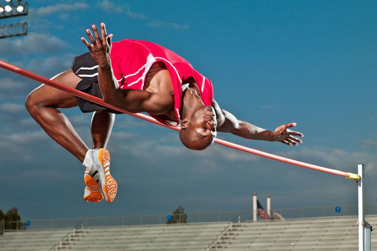 African American male High jumper clearing the high jump bar, athletic track event
