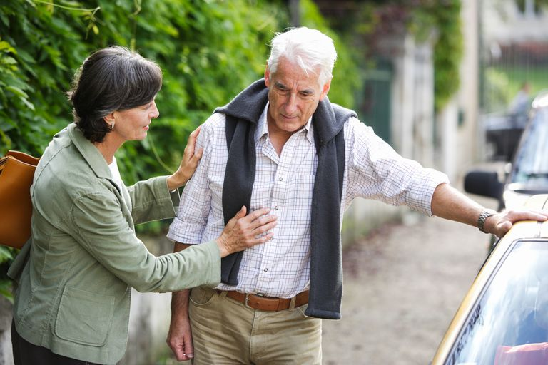 Elderly man leaning against car with wife helping him