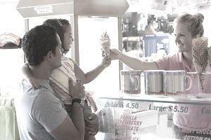 Waitress handing ice cream cone to young girl