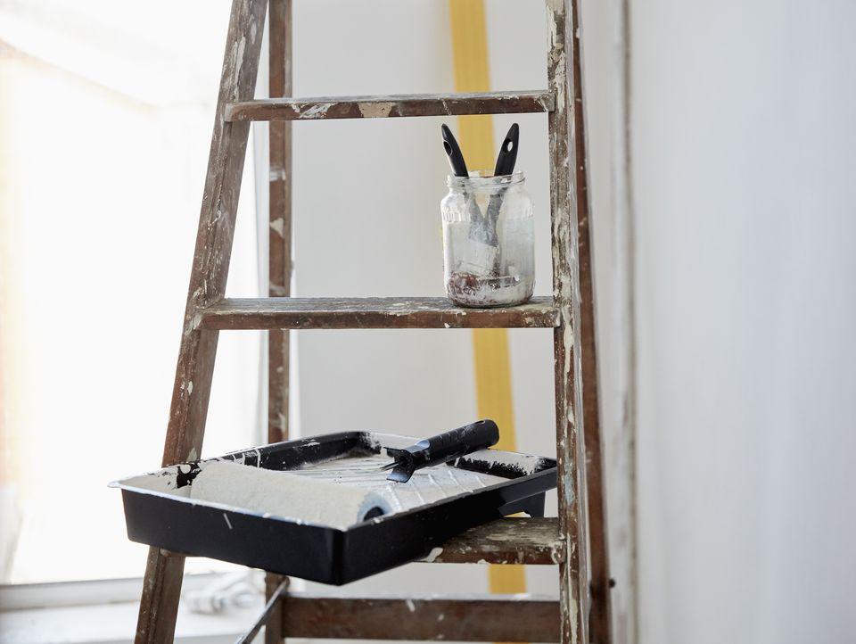 A wooden paint splashed ladder, a jar with two paintbrushes and a paint tray and roller.