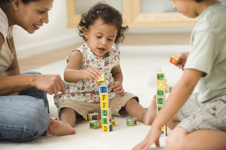 Hispanic mother playing on floor with son and daughter