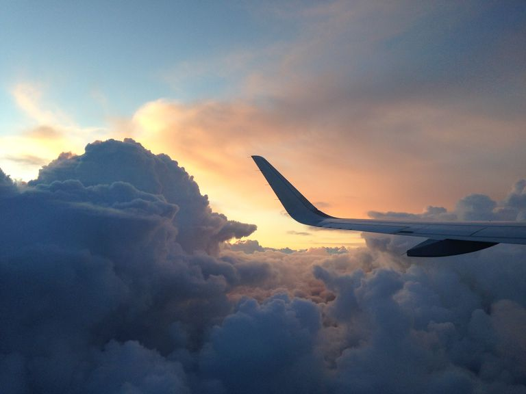 Commercial airplane against a soft sunset and clouds.