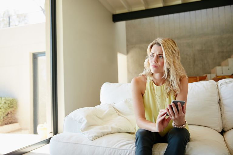 Anxious woman sitting on a couch using her smartphone to connect with a mental health counselor.