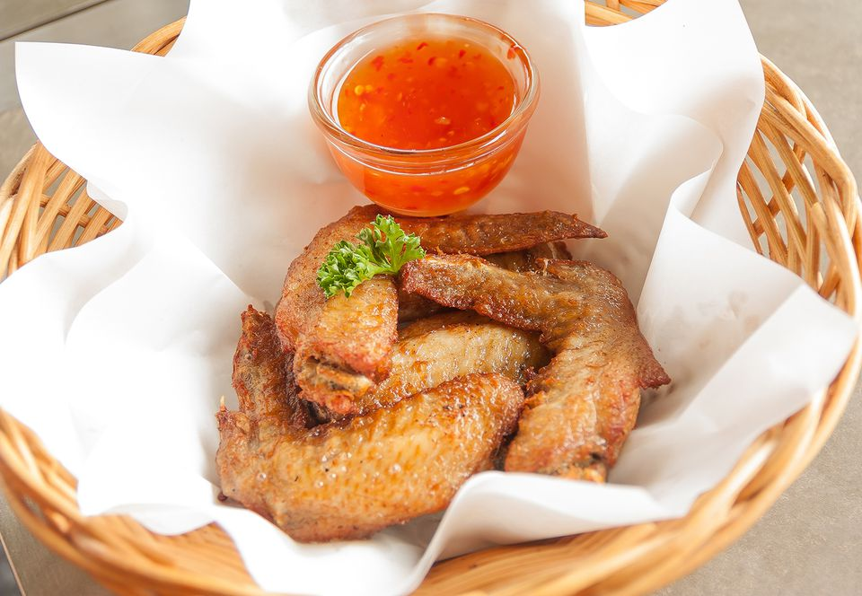 High Angle View Of Fried Chicken Wings With Sauce In Basket