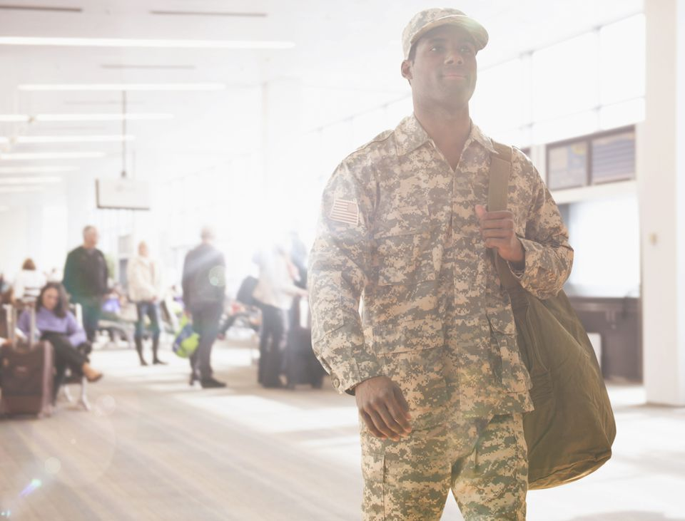 African American soldier carrying bag in airport