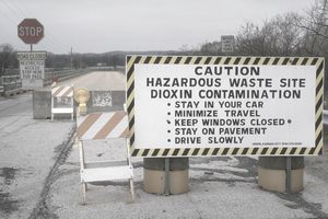 A bold sign warns caution before a hazardous waste site due to dioxin contamination