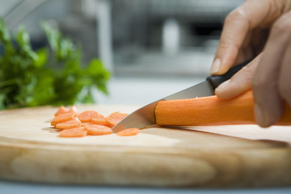 Close up of hand chopping carrot