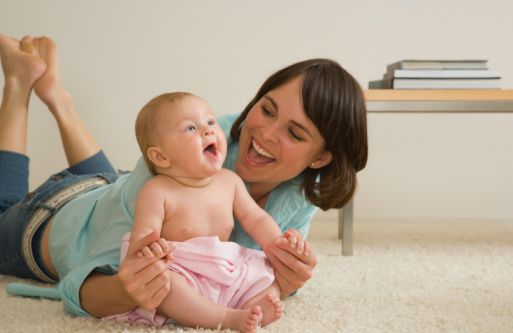 Mother on floor playing with baby