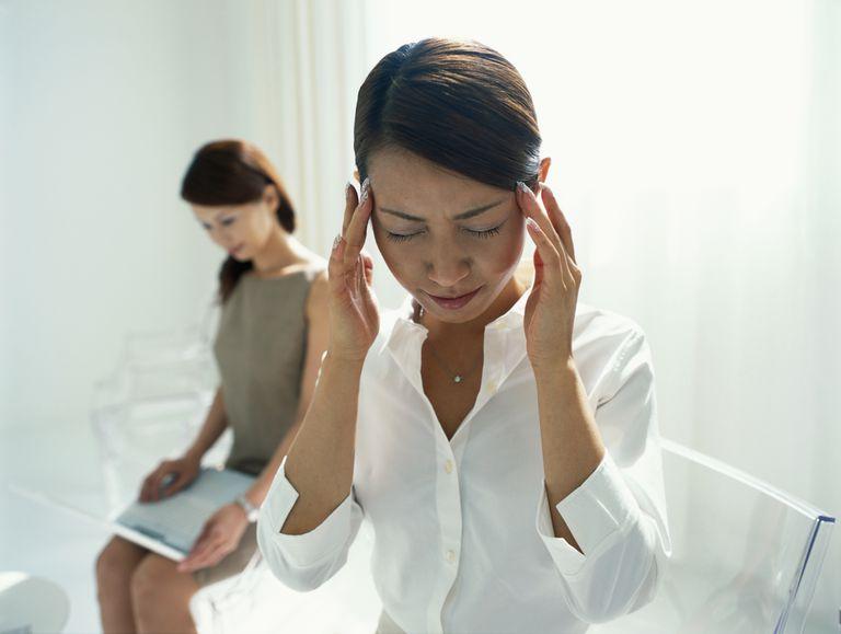 dizzy Asian woman holding head