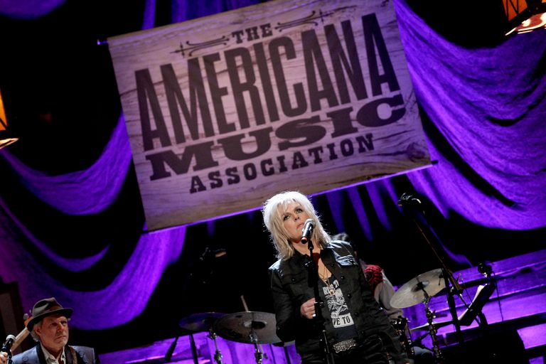 Lucinda Williams on stage in front of AMA poster.