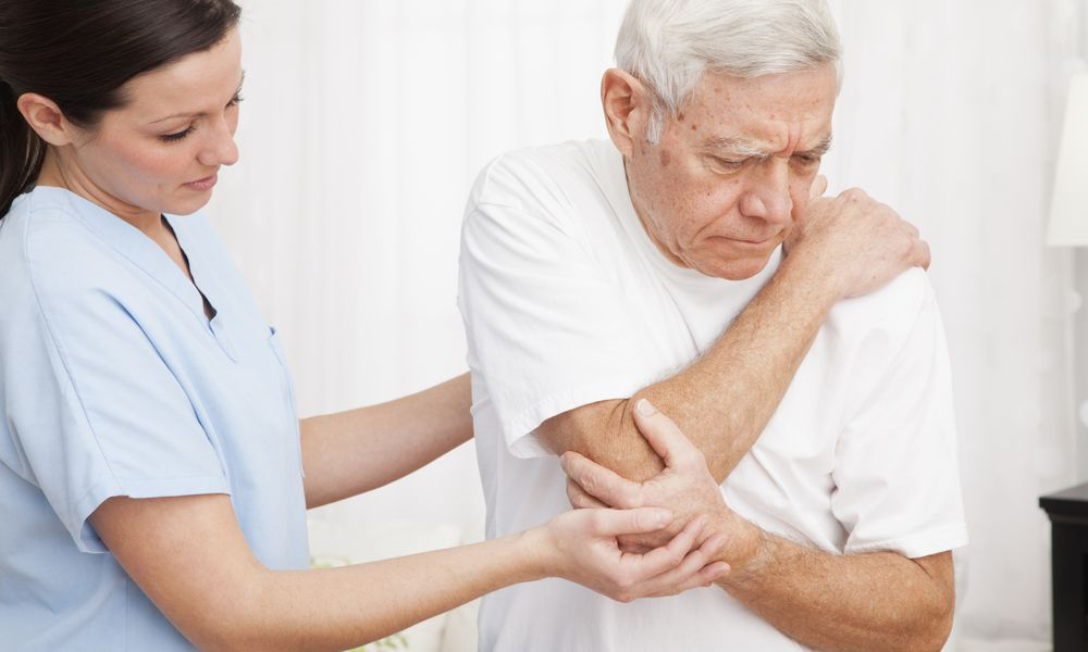 Photo of a PT helping elderly man with elbow pain.