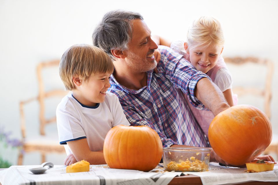 a father his son and his daughter hollowing out pumpkins for halloween - Wheeler Farm Halloween