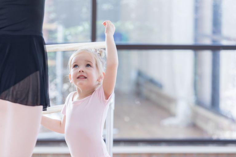 Adorable little ballerina listens to instructor at ballet barre