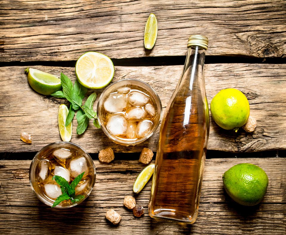 A bottle of rums, limes and mint on a wooden table.