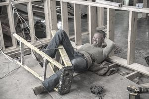 a injured construction worker wrapped up in a ladder and holding his head