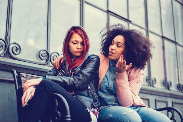 Young woman calming a depressed friend