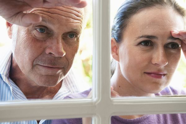 two parents peeking out a window