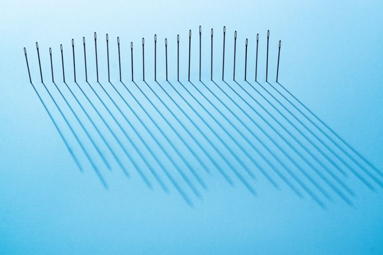 A row of evenly-spaced sewing needles of various heights casting long shadows