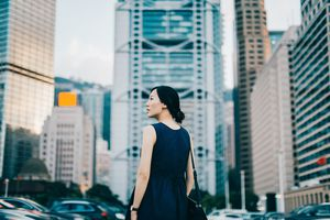 Woman looking at large buildings in city insurance company choices concept