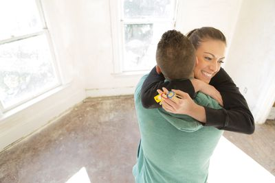 Couple hugging with keys to their new home