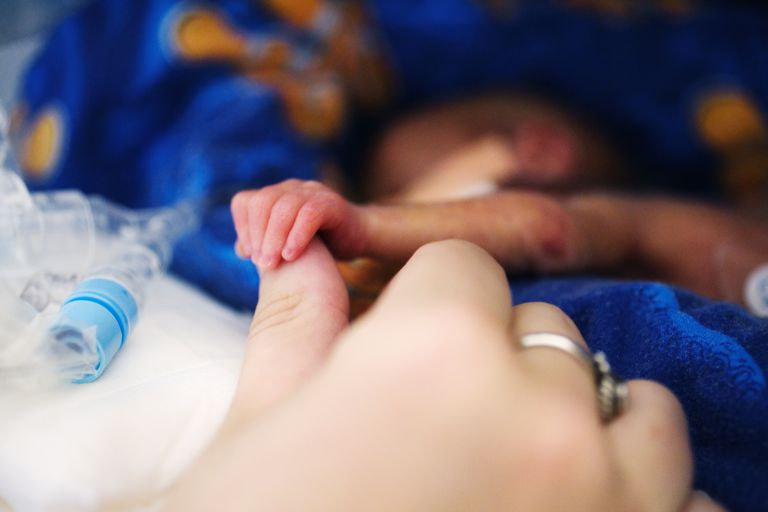 Premature baby boy (0-3 months) in incubator, holding mother's thumb