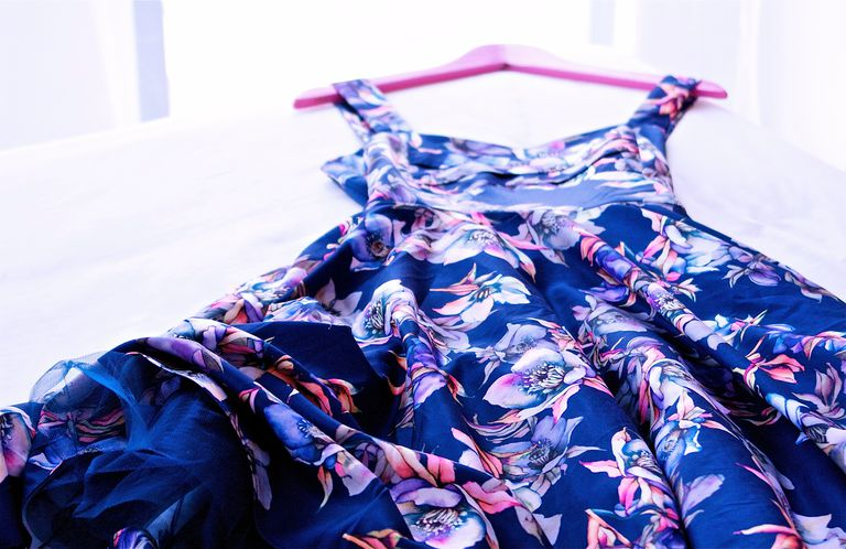 Blue dress with purple flowers laying on a bed