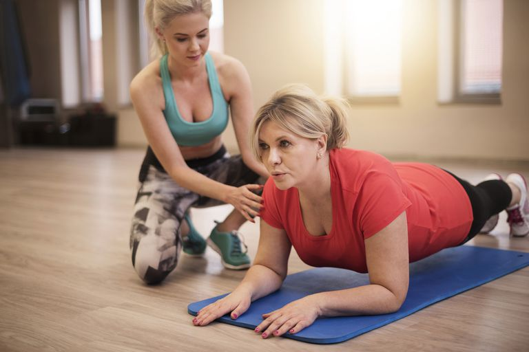 Woman doing plank with instructor adjusting her form