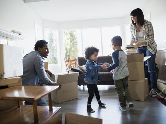 Family unpacking moving boxes in living room