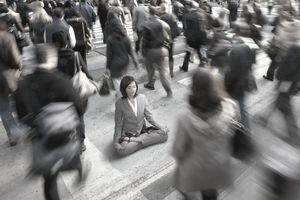 Businesswoman meditating in the middle of a busy commuter crowd